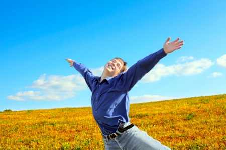 Happy Young Man raising his Hands in the Summer Field Stock Photo - 16762975