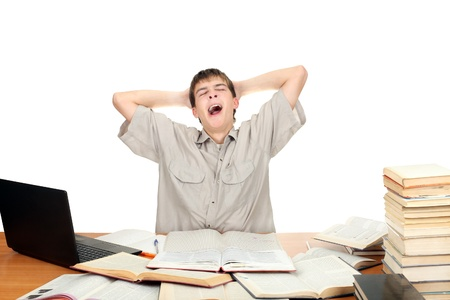 Tired Student Yawning on the School Desk  Isolated on the White photo