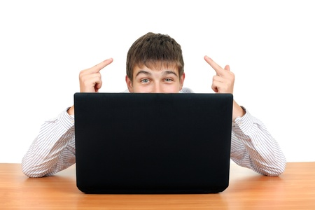 indecent: Young Man Shows Middle Fingers Gesture behind Laptop  Isolated on the White Background