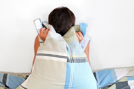 Sad Teenager sitting with pillow on the Bed in Home interior Stock Photo - 16908022