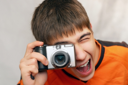 Excited Teenager with Photocamera gets ready to take a photograph photo