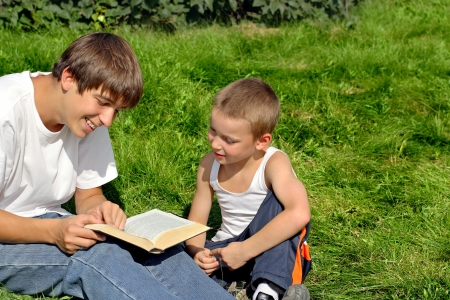 Older and Little Brothers reads a Book in the Summer Park photo