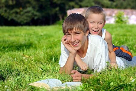 Happy Brothers lying on the Grass with a Book in the Summer Park Stock Photo - 17593329