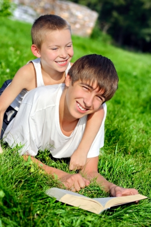 Happy Brothers lying on the Grass with a Book in the Summer Park photo