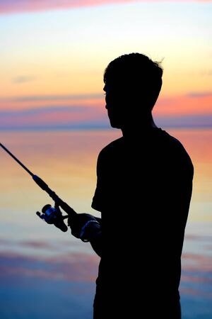 Fisherman silhouette with fishing-rod on sunset background photo