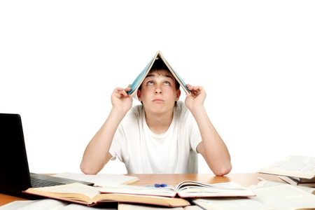 Student at the school desk with many books cover his head with exercise book Stock Photo - 17796651