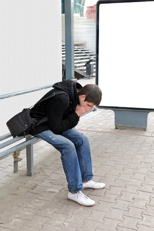 Sad Young Man Sitting at the Bus Stop at the City Street