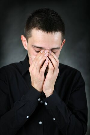 sorrowful: Sorrowful Young Man Portrait in the Black Shirt on The Dark Background