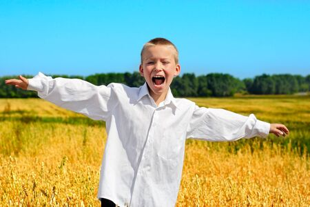 Happy Boy in white shirt at the summer wheat field photo