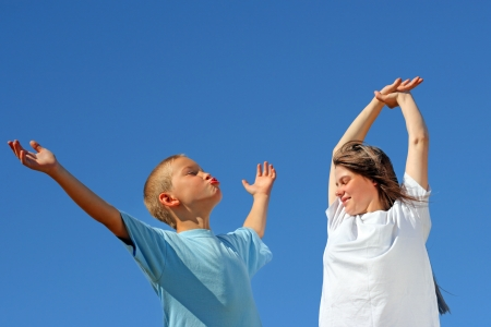 Young Boy and Teenage Girl with hands up on the Blue Sky Background photo