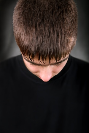 Portrait of Teenager With Lowered Head on the Black Background photo