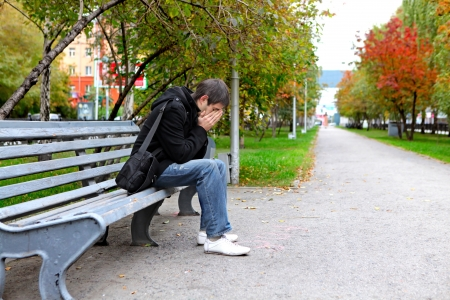 Sad young man sitting on the bench outdoor photo