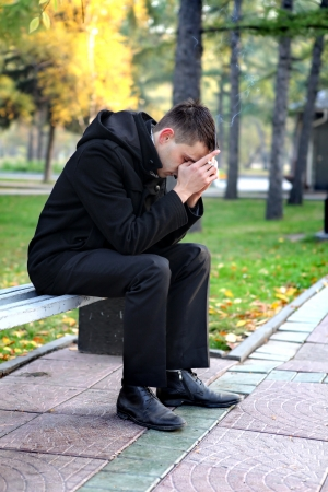 sorrowful: Sorrowful man sitting and smoking on the bench in the autumn park Stock Photo