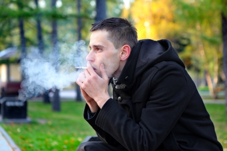 man smoking: Sad man smoking cigarette in the autumn park Stock Photo
