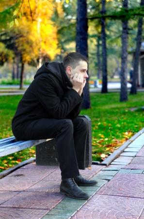 uneasiness: Hombre joven triste que se sienta en el banco en el parque de oto�o Foto de archivo