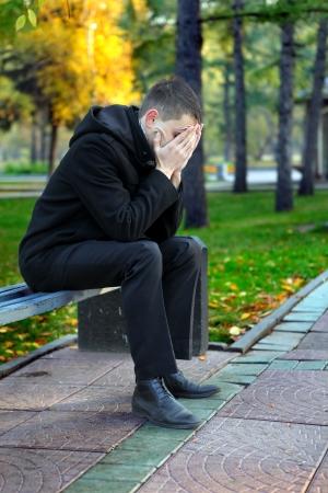 uneasiness: Hombre joven triste que se sienta en el banquillo al aire libre