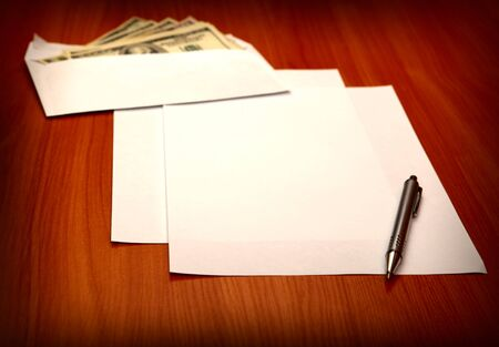 payola: Envelope with a Money and Empty Paper for Text on the Wooden Table