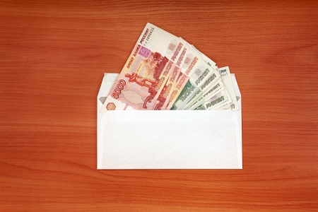 payola: Envelope With Russian currency lying on the table Stock Photo