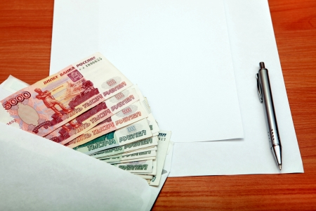 payola: Envelope with a Russian Money and Empty Paper for Text on the Wooden Table Stock Photo
