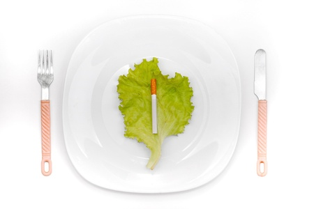 deleterious: Cigarette on the lettuce leaf in the dinner plate Stock Photo