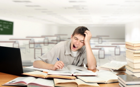 Bored Student is Yawning at the School Desk in the Classroom photo