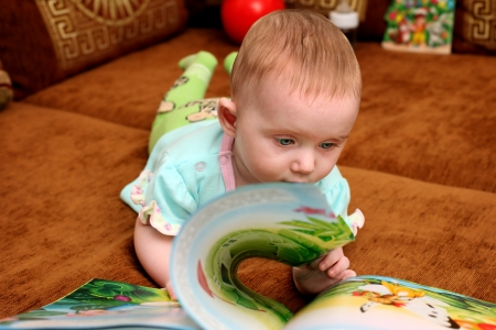 Curious Little Baby with a Book on the Sofa Stock Photo - 18822087