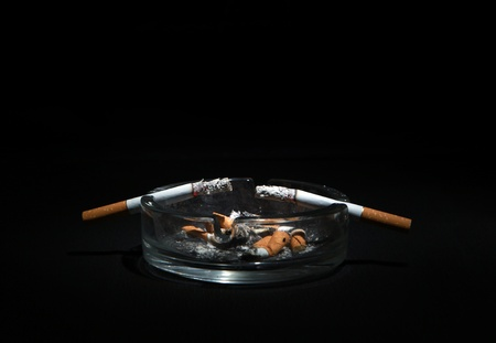 Dirty Ashtray And Two Cigarette On the Dark Background Stock Photo - 18868056