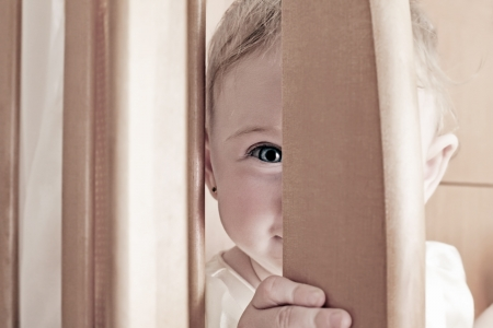hide and seek: Toned Photo of Cheerful and Sly Little Baby Playing Hide and Seek