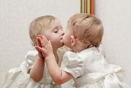 mirar espejo: Beb� lindo que besa un espejo con uno mismo Reflection Foto de archivo