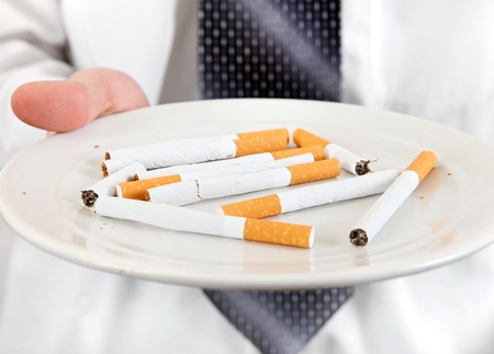 deleterious: Man Holding Plate with Many Cigarettes closeup  Isolated on the white background