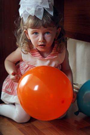 Little Girl sitting under table and playing hide and seek photo