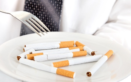 deleterious: Man Hold a Fork and Plate with Many Cigarettes closeup