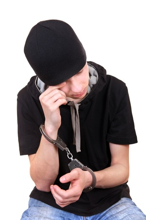 malefactor: Man in Handcuffs is Weeping Isolated on the White Background Stock Photo