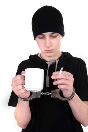 Man in Handcuffs with Cigarette and the Mug Isolated on the White Background photo