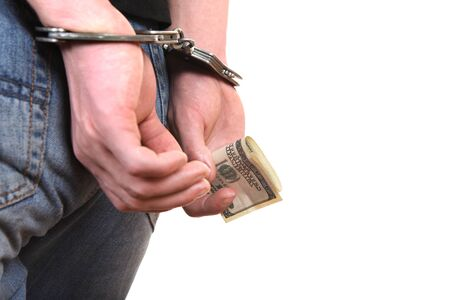 payola: Handcuffs on the Hands with a Money Closeup Isolated on the White Background