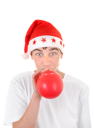 to inflate: Teenager in Santas Hat inflate Red Balloon Isolated On The White Background
