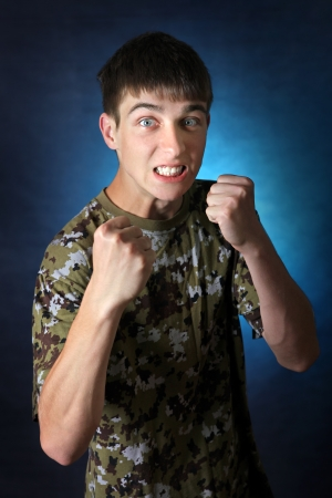 bared teeth: Angry Teenager in camouflage t-shirt threaten with his fists. On the Dark Background
