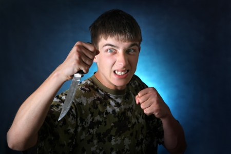 bared teeth: Angry Teenager with Knife On the Dark Background