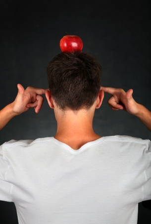 occiput: Rear View of the Man with an Apple on his Head on the dark background