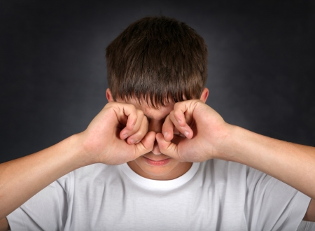 Young Man Rub his Eyes on the dark background