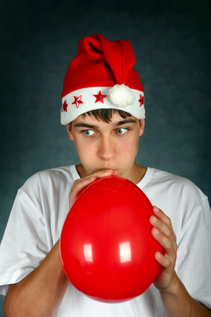 Teenager in Santas Hat inflate Red Balloon On the Dark Background photo