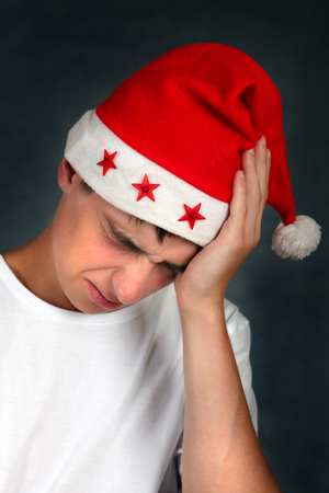 after the party: Young Man in Santas Hat feels headache after Party
