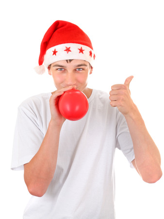 Teenager in Santas Hat inflate Red Balloon and Pointing up Isolated On The White Background photo