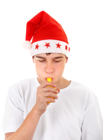to inflate: Teenager in Santas Hat trying to inflate a Balloon Isolated On The White Background