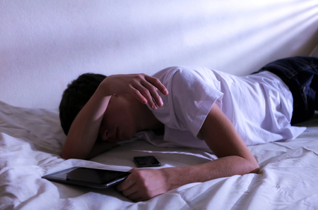 the weariness: Tired Young Man Sleeps with Tablet Computer on the bed In the Dark Room