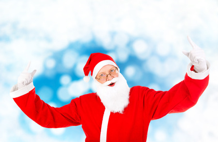 Cheerful Santa Claus with Hands Up on the Abstract Winter  photo