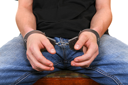 Front view of the Man in Handcuffs on the White Background Closeup photo