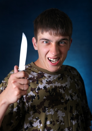 bared teeth: Angry YOung Man with a Knife On the Dark Background