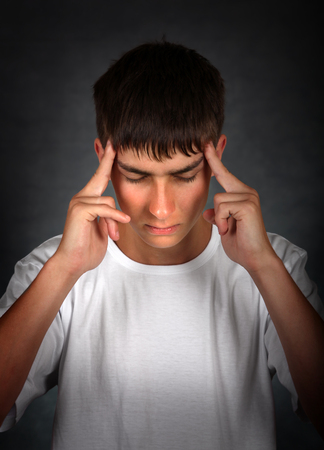 unrest: Young Man Feels Headache on the dark background