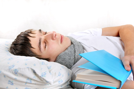 drowse: Tired Young Man Sleeps with a Book on the bed